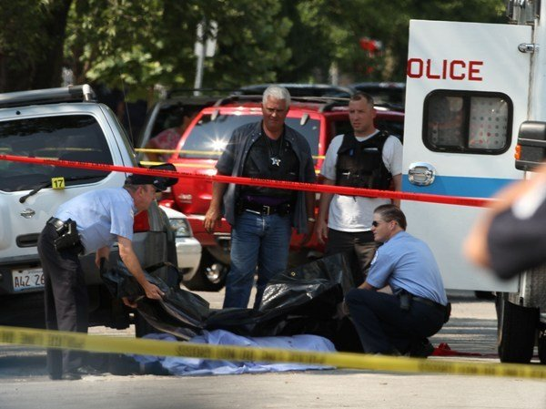 Police prepare to put a teen shooting victim into a body bag in the 5800 block of S. Fairfield, another teen was being hospitalized for a leg wound.. July 12, 2012, 2012 (Phil Velasquez Chicago Tribune)   B582234366Z.1 ....OUTSIDE TRIBUNE CO.- NO MAGS,  NO SALES, NO INTERNET, NO TV, CHICAGO OUT, NO DIGITAL MANIPULATION... keywords: chicago police department shooting South Side  BNC TEXT: A 16-year-old boy was killed and another boy, 15, was wounded this afternoon in a shooting in the city's Gage Park neighborhood that police say is gang-related. The shooting happened shortly after 2 p.m. on the 5800 block of South Fairfield Avenue, said Police News Affairs Officer Darryl Baety. Police said both teens, who live across the street from each other on the block where they were shot, have criminal histories and identify with the same local gang. Police say two male attackers ran toward the teens from behind a tree. Both teens tried to run and one of the attackers opened fire, hitting the pair. The older boy was dead at the scene and the other suffered wounds to his legs in the shooting, police said. A Chicago Fire Department ambulance took the second victim in serious-to-critical condition to Advocate Christ Medical Center in Oak Lawn. They were a couple doors down from where they lived when they were shot, police said.